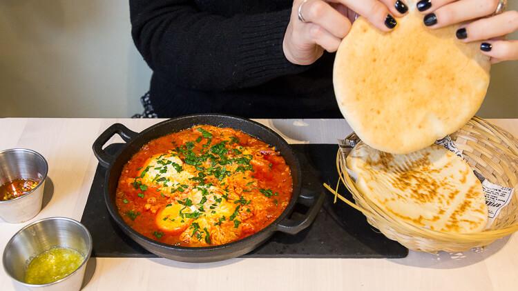 BAR GANZO Sakshuka, con huevos escalfados en salsa de tomate (matbucha), tahina y perejil